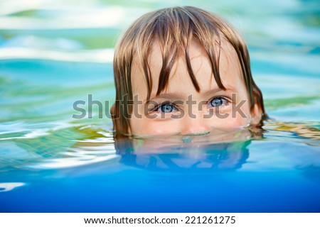 Little girl swimming in a pool - stock photo