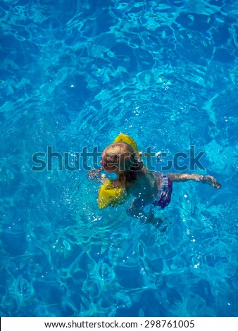 Little girl swimming in the swimming pool - stock photo
