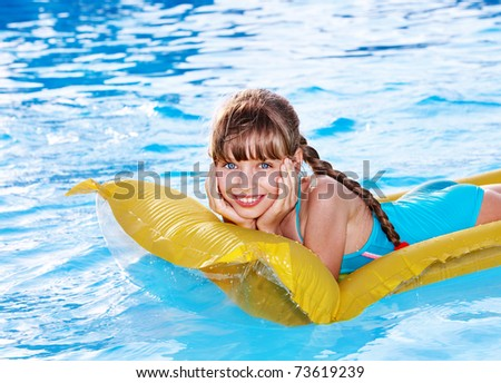 Little girl swimming on inflatable beach mattress. - stock photo