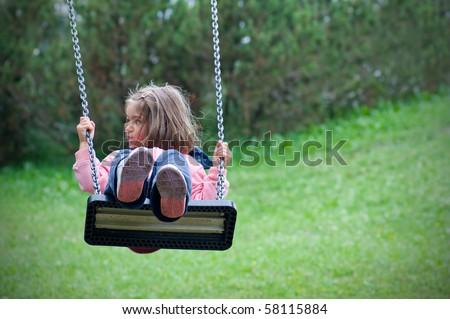 Little girl swinging. - stock photo