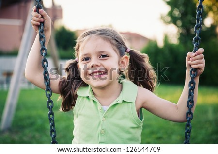 Little girl swinging close up portrait. - stock photo