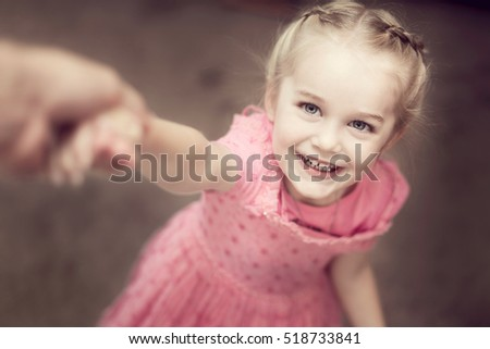 little girl swinging from her parents hands
