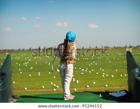 Little girl swinging golf club, rear view - stock photo