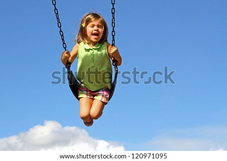 Little girl swinging high above clouds - stock photo