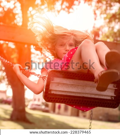 Little girl swinging in a park - stock photo