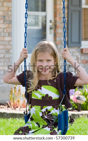 Little Girl Swinging in Front of Her House - stock photo