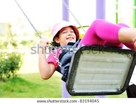 Little girl swinging in park - stock photo