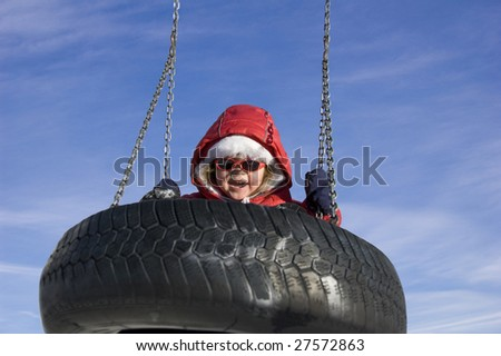 little girl swinging in the winter, blue sky in the background - stock photo