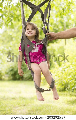 Little girl swinging on a parachute straps