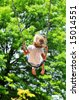 Little girl swinging on a sunny day with trees in the background - stock photo