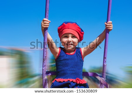 Little girl swinging on a swing against the blue sea. - stock photo