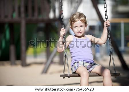little girl swinging on playground alone - stock photo