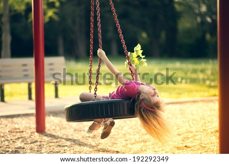 Little girl swinging on swing at park. - stock photo