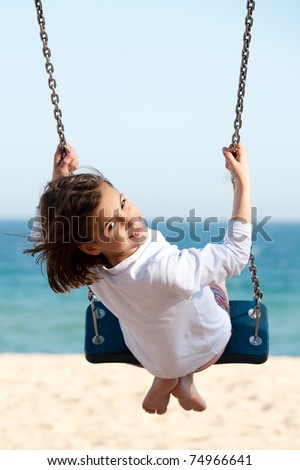 Little girl swinging with the sea in the background - stock photo
