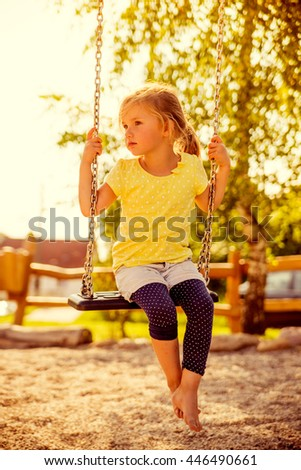 little girl swings while sun set - stock photo