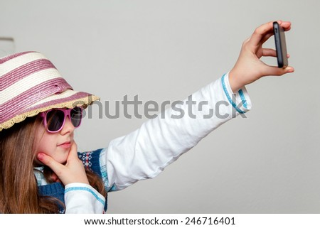 Little girl takes selfie with mobile phone - stock photo