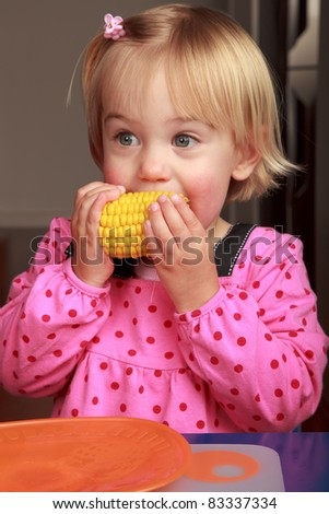 Little girl taking a bite out of a corn cob - stock photo
