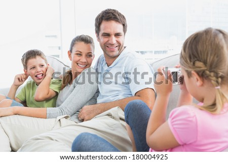 Little girl taking a photo of her family on the couch at home in the living room - stock photo