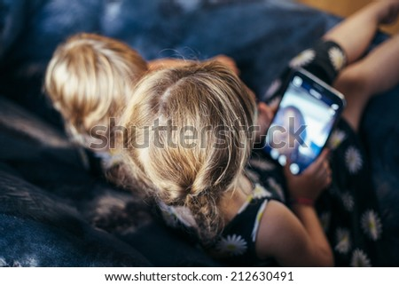 Little girl taking a selfie using tablet computer on the couch - stock photo