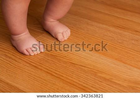 Little girl taking her first steps on some hardwood floor - stock photo
