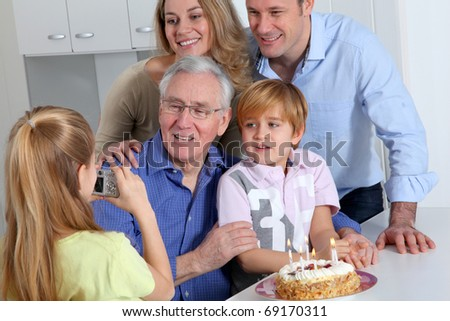 Little girl taking picture of family on birthday celebration - stock photo