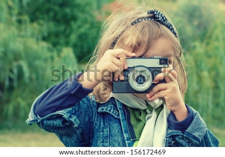 Little girl taking  picture using vintage film camera