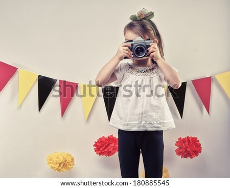 Little girl taking pictures with a vintage film camera. - stock photo
