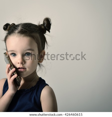 Little girl talking mobile phone. Child using a mobile phone. - stock photo