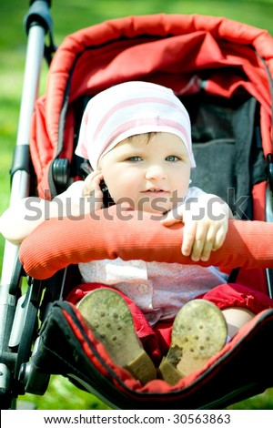 little girl talking mobile phone in baby carraige - stock photo