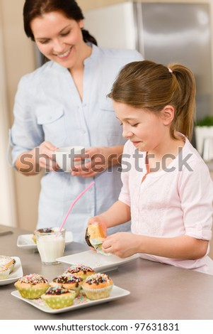 Little girl taste sprinkles cupcakes with mum happy at home - stock photo