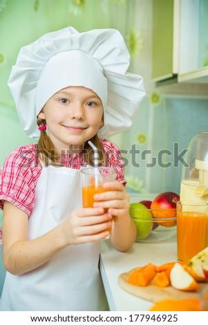 Little girl tastes freshly prepared apple-carrot juice - stock photo