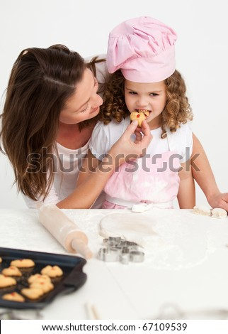 Little girl tasting a biscuit with her mother in the kitchen