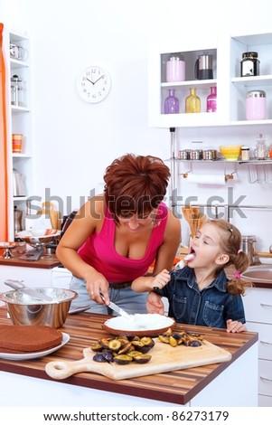 Little girl tasting the cream of the cake - stock photo