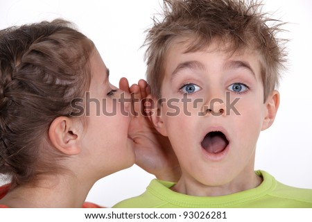 little girl telling a boy a secret - stock photo