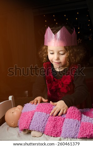 Little girl telling bedtime stories to her doll