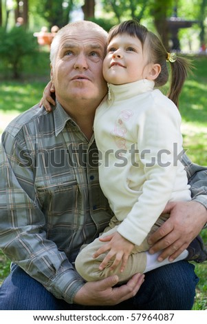 Little girl tenderly embraces grandfather and sits on his arms in the park. Both look up - stock photo