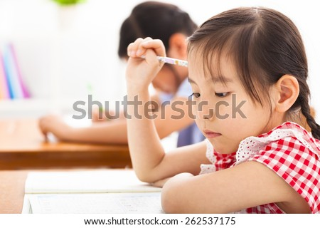 little girl thinking in the classroom - stock photo