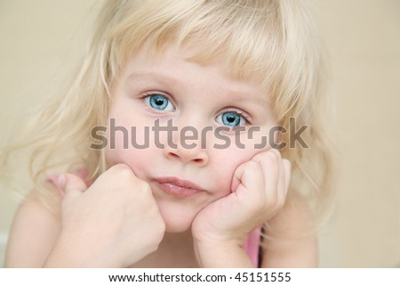 little girl thinks, look at the camera - stock photo