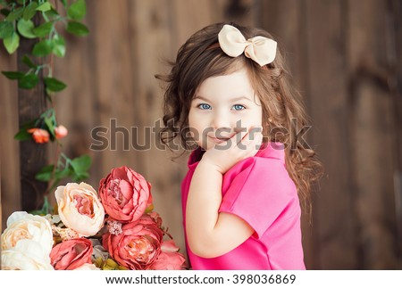 little girl three years old with brown wavy hair and bow sits on a wooden ladder with Becket beautiful peony flowers and smiling with his hand propping up his head - stock photo