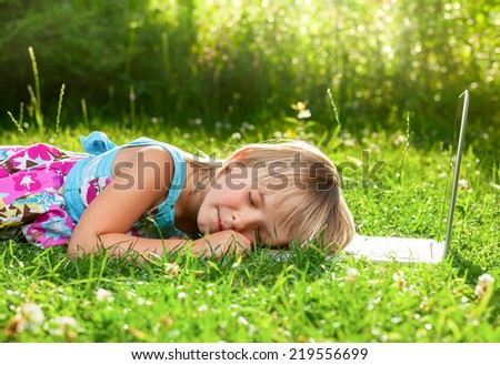 Little girl tired to use laptop and fell asleep in a summer garden - stock photo