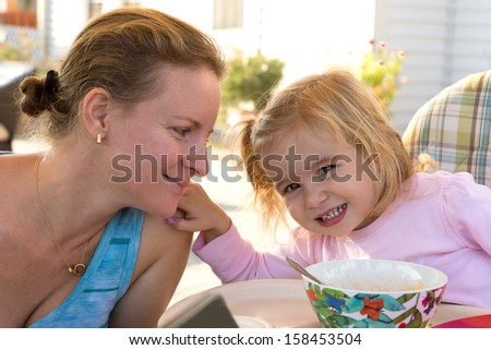 Little girl toddler touching her mothers shoulder softly while mother looks at her daughter at the table