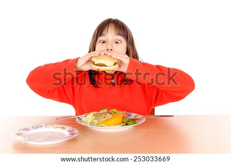 little girl torn between hamburguer and vegetables isolated in white background - stock photo