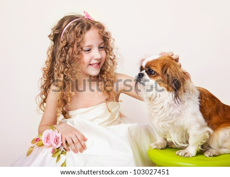 little girl touches small dog