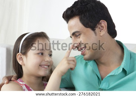 Little girl touching father's nose at home - stock photo