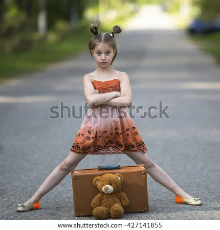 Little girl traveler with suitcase and Teddy bear is on the road. - stock photo