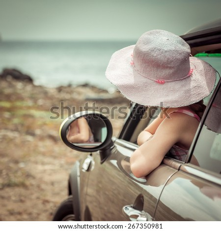 little girl traveling by car at sea back view - stock photo