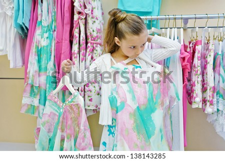 Little girl tries on dress in clothing store - stock photo