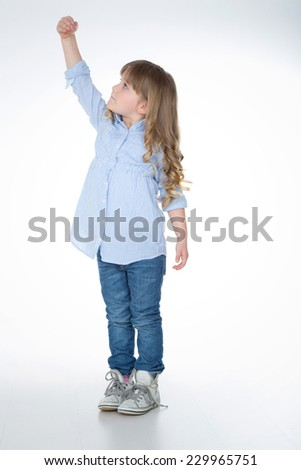 little girl tries to reach something with hand - stock photo