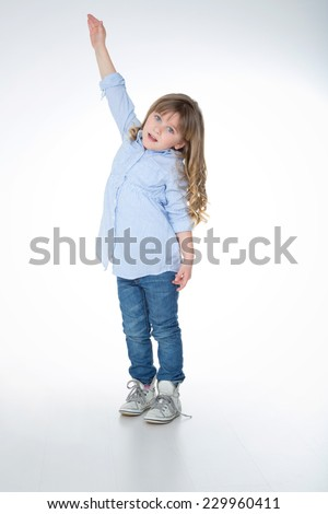 little girl tries to reach the top of something - stock photo
