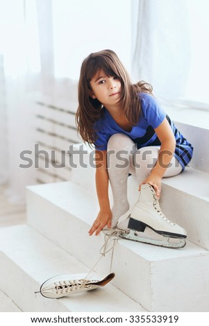 Little girl trying on a large ice skating. Little kid and skates - stock photo